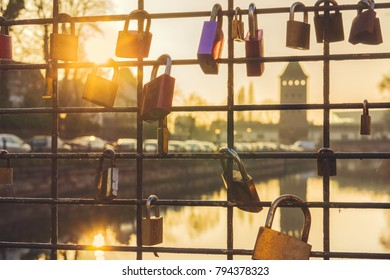 Some love locks attached to the metal grid of a bridge, Strasbourg, France.