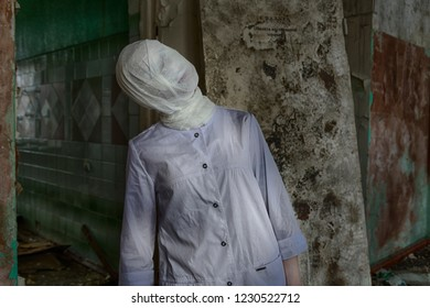 Some man or woman with bandaged face in medical gown inside ruined medical clinic or asylum. Maybe plastic surgery patient, or ghost or zombie creature from horror movie scene