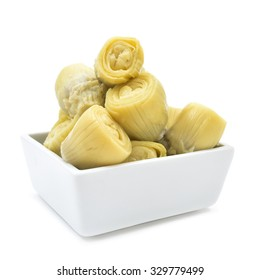some marinated artichoke hearts in a rectangular white bowl on a white background