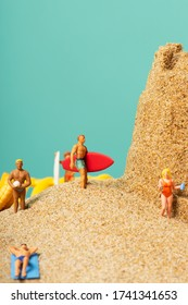 some miniature people in swimsuit carrying surfboards or relaxing on the sand of the beach, next to a sandcastle, against a blue background with some blank space on top