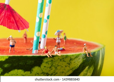 some miniature people wearing swimsuit relaxing on a refreshing ripe watermelon, with some white and blue drinking straws and a paper umbrella stuck in it, against a yellow background