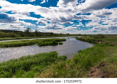 Some minutes before a thunderstorm. Sun rays over the river. Belarusian nature. Forest Lake. Summer, green grss, meadow. Reflection of sun rays in water.