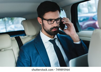 Some misunderstood. Handsome young businessman using laptop and talking on mobile phone while sitting in car