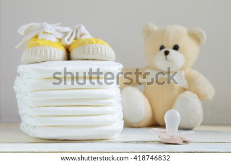 Some nappies on a white wooden table. Sneakers, a pacifier and a teddy bear. Empty copy space for editor's text.