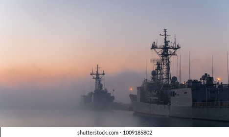 Some navy frigates and destroyers in port during a cold and foggy morning in a naval base. A fog bank between ships in port during a cold sunrise.