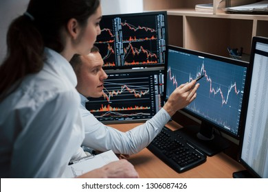 Some nice results. Team of stockbrokers are having a conversation in a office with multiple display screens.