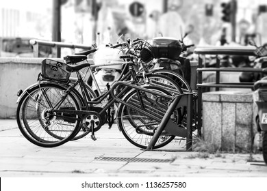 Some old bikes parked on the street in Milan city in Italy, in a black and white vintage photo.