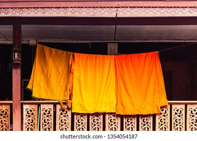 Some orange monk's clothes hanged to a laundry thread to dry on the balcony of a wooden buddhist temple