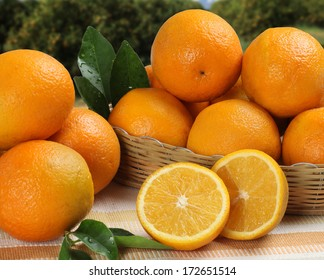 Some oranges in a basket over a wooden surface on a orange field as background