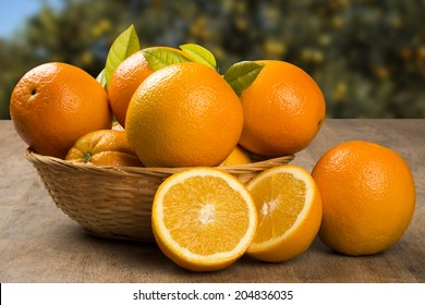 Some oranges in a basket over a wooden surface on a orange field background