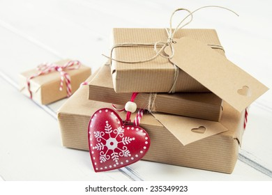 Some paper parcels wrapped tied with tags. A red heart and some  christmas gift boxes wrapped with paper kraft and tied with red & white baker's twine on a white wooden table. Vintage Style.