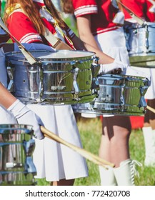 Some parade snare drummer on the girls in red uniforms at a summer music festival