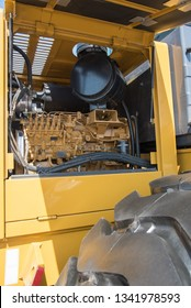 Some parts from a large yellow car for transportation of ore called Belaz, black wheels, blue stairs and others at the exhibition coal and mining