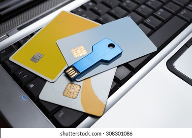 Some pay card and usb key on laptop keyboard