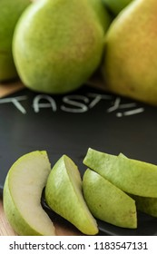 Some pears unfocussed on a table behind a black cutting board with the unfocussed inscription Tasty. The focus lies on the pieces of pears in the foreground.