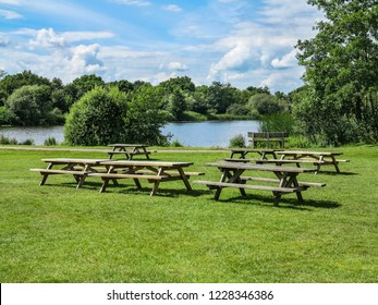 Some picnic tables with a lake and trees behind