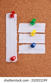 Some pieces of blank note paper are pinned to a cork board.
