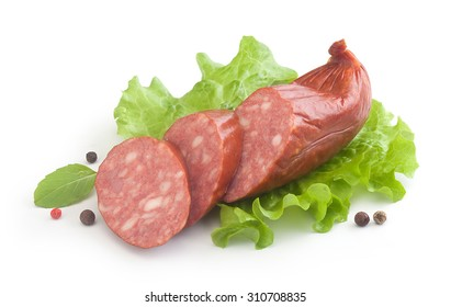 Some pieces of smoked sausage with fresh green lettuce, basil and black pepper on the white