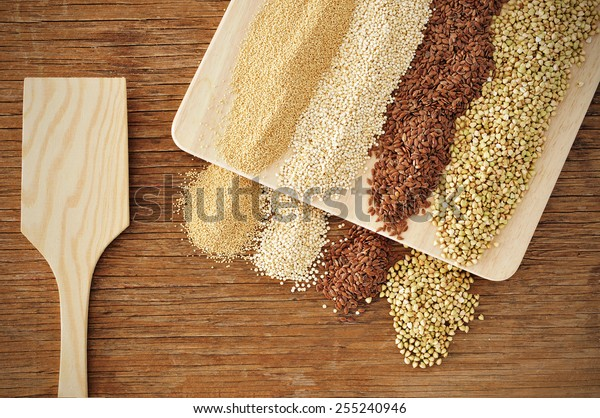 some piles of amaranth, quinoa, brown flax and buckwheat seeds on a rustic wooden table