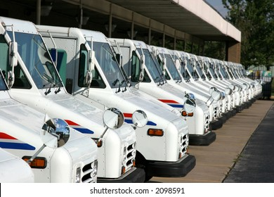 Some postal delivery trucks in line