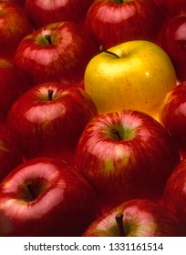 some red apples and one yellow forming a texture, concept of singularity