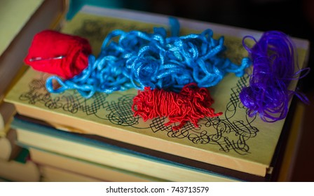 Some red, blue and purple antique ropes laying on a stack of old books.