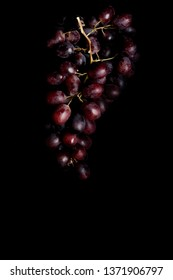 some red grapes shot in a black box, high contrast