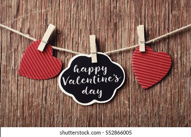 some red hearts hung with clothespins in a clothes line and a signboard in the shape of a thought-bubble with the text happy valentines day, against a rustic wooden background