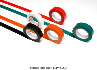 some rolls of colored insulating tape on a white surface