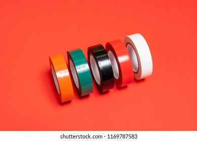 some rolls of colored insulating tape on a red surface