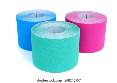 some rolls of elastic therapeutic tape of different colors, pink and two different shades of blue, on a white background