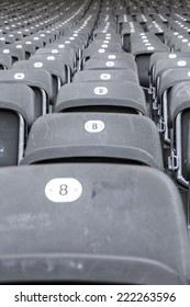 some rows of gray stadium seats, shoot from the front