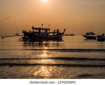Some ships silhouette on the sea of Thailand. Slowly the sun goes down and people come to rest on the wavy sea.
