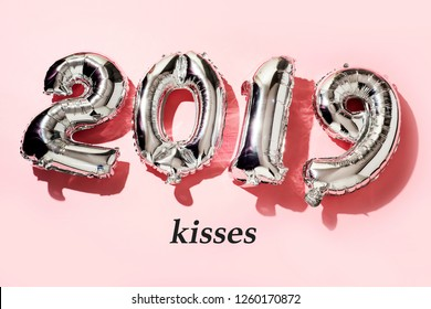 some silvery number-shaped balloons forming the number 2019, as the new year, and the word kisses against a pink background