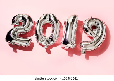 some silvery number-shaped balloons forming the number 2019, as the new year, on a pink background