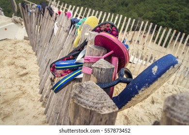 Some slippers or flip-flops hanging on a wooden fence at the beach