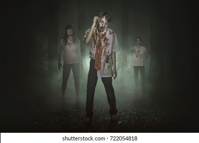 Some spooky asian zombies with blood walking around in the misty forest