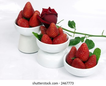 some strawberry little bowls with mint on white background and one valentine rose