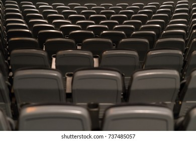 Some symmetrical grey seat sows in a cinema.