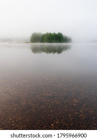 Some trees just barely visible through the fog before dawn on Powder Mill Pond in Bennington New Hampshire