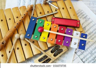 Einige typische, farbenfrohe Musikinstrumente, die hauptsächlich von Kindern verwendet werden. Die musikalische Partitur im Hintergrund ist in der Public Domain.