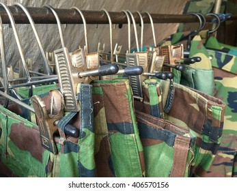 some used soldier clothes hanging on a rack in a flea market in Thailand