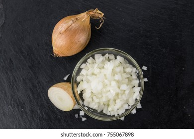 Some White Onions (dices) on a slate slab as detailed close-up shot; selective focus
