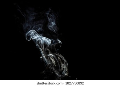 some white smoke rising against a black background