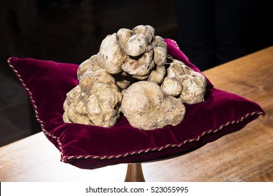 Some white truffles on a red pillow, on the bottom a wooden table