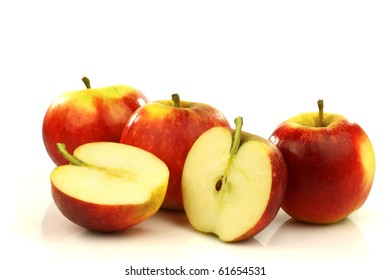 some whole and some cut red and yellow apples on a white background