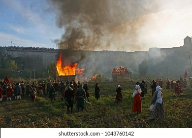 Some wooden houses are on fire during the historical reenactment of Battle of Kamianets-Podilsky (1653) (Ukraine). Living history festival. Re-enactors stand in cannon smoke before the final battle