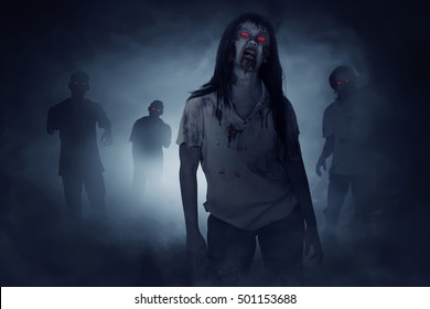 Some zombies walking around on the foggy night