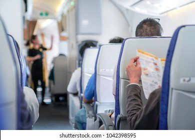 somebody is reading the menu on the seat in the plane, and ready to order to air hostess.