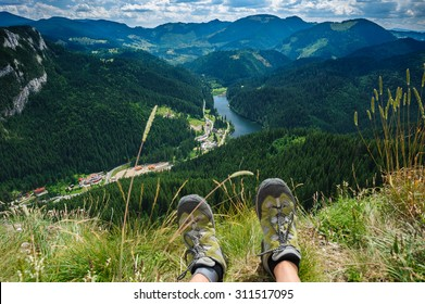 Somebody is sitting at the edge of cliff in mountains, showing his feet wearing hiking shoes. First person shoot. Retezat area, Carpathians, Romania